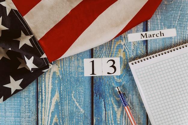 3月13日カレンダー日空のメモ帳とオフィスの木製テーブルの上のペンで自由と民主主義のアメリカ合衆国のシンボルの旗