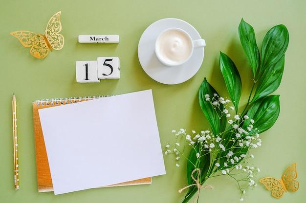 木製キューブカレンダー3月15日。メモ帳、一杯のコーヒー、緑の背景に花束の花。コンセプトこんにちは春