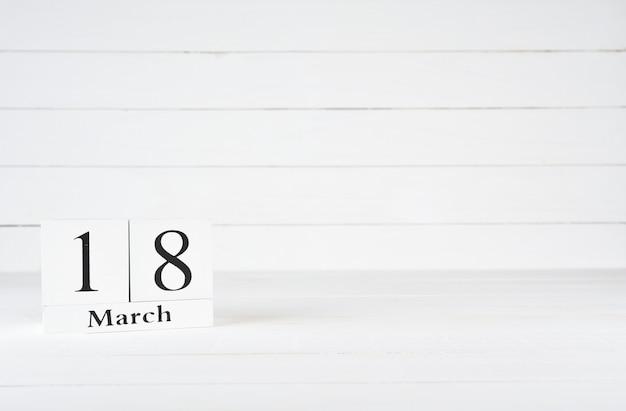 3月18日、月18日、誕生日、記念日、テキスト用のコピースペースを持つ白い木製の背景に木製のブロックカレンダー。