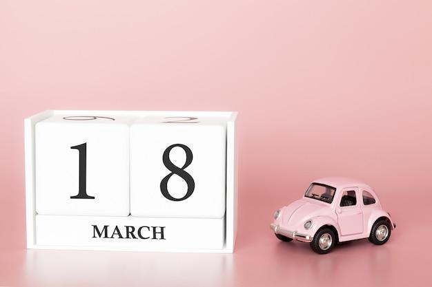 木の立方体は3月18日です。 3月の18日目、レトロな車とピンクの背景のカレンダー。