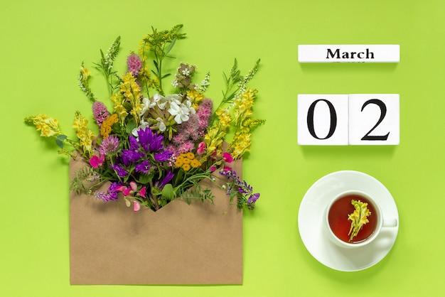 木製キューブカレンダー3月2日。ハーブティー、緑色の背景でマルチカラーの花とクラフト封筒。コンセプトこんにちは春クリエイティブトップビューflat lay
