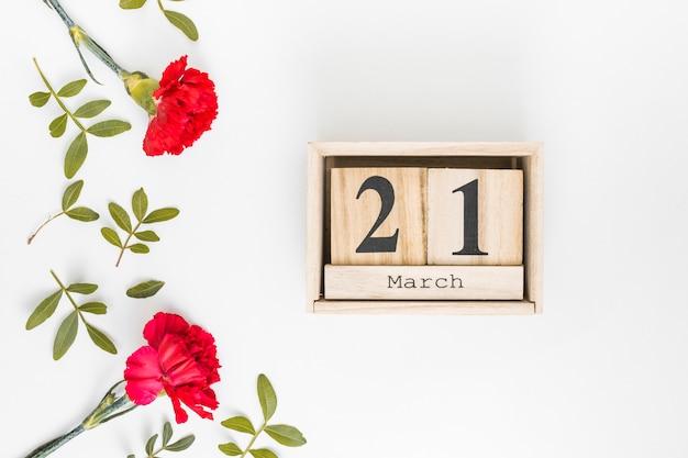 カーネーションの花を持つ3月21日碑文