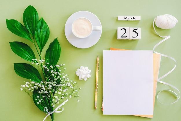 3月25日。メモ帳、一杯のコーヒー、緑の背景に花束の花。コンセプトこんにちは春