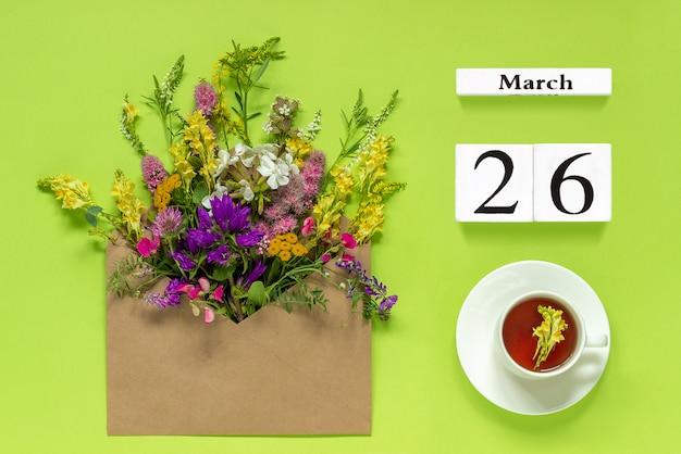 木製の3月26日。一杯の紅茶、グリーンのマルチカラーの花とクラフト封筒