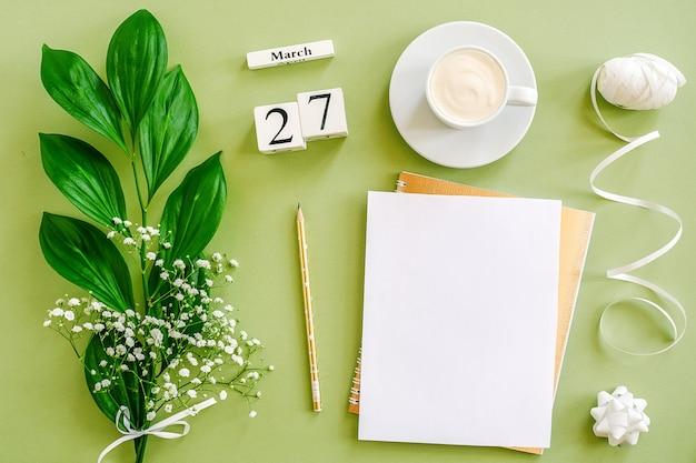 木製キューブカレンダー3月27日。メモ帳、一杯のコーヒー、緑の背景に花束の花。コンセプトこんにちは春