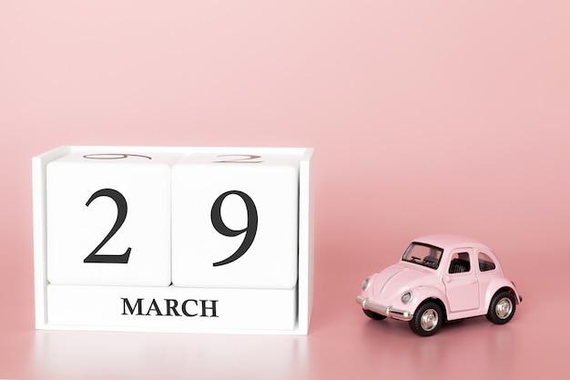 木の立方体は3月29日です。 3月の29日、レトロな車とピンクの背景のカレンダー。