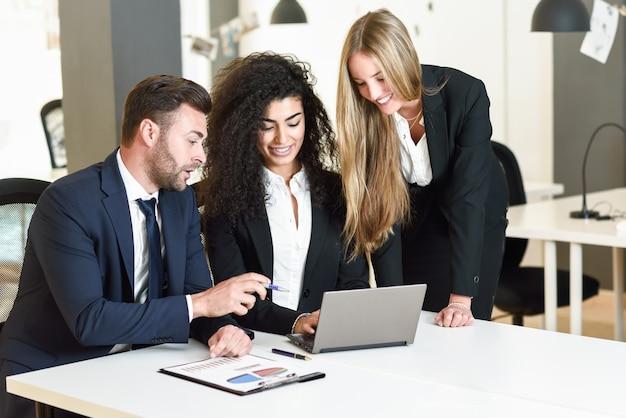 現代的なオフィスで3人のビジネスマンを集めた多民族グループ。 2人の女性とラップトップコンピュータを見ているスーツを着ている白人男性。