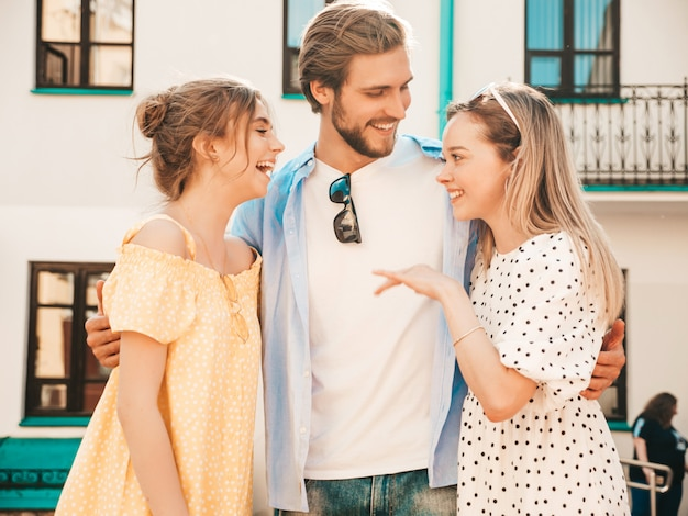 通りでポーズをとる若い3人のスタイリッシュな友人のグループ。ファッション男とカジュアルな夏服を着た2人のかわいい女の子。サングラスで楽しい笑顔のモデル。陽気な女性とチャットの男
