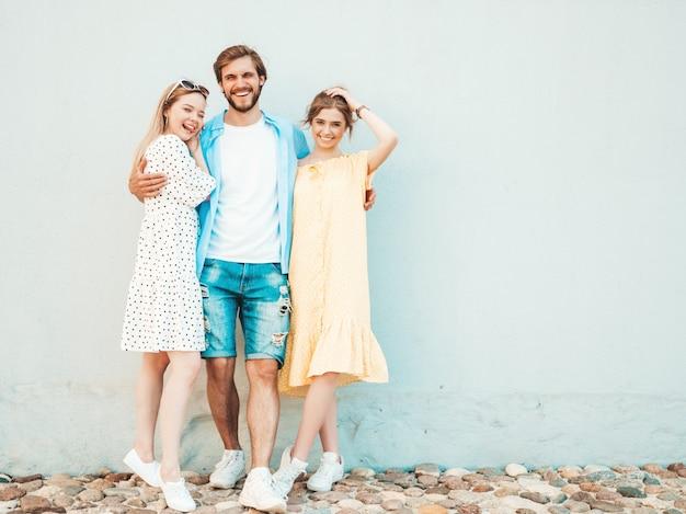 通りでポーズをとる若い3人のスタイリッシュな友人のグループ。ファッション男とカジュアルな夏服を着た2人のかわいい女の子。壁の近くで楽しんでいる笑顔のモデル。陽気な女性と屋外の男