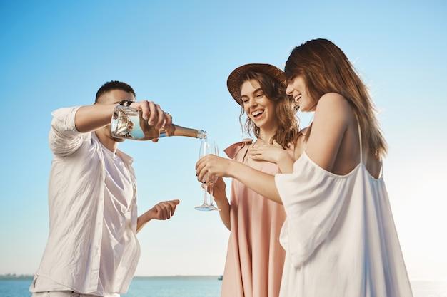 休暇中にヨットで旅行し、シャンペーンを飲んで、新鮮な海の空気を楽しんでいる魅力的な3人の若者の肖像。友人は、2人の女性をボートに招待し、夏の始まりを祝いました。