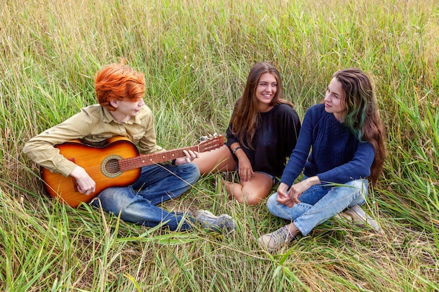夏休み休暇音楽幸せな人々の概念。 3人の友人の男の子と屋外で一緒に楽しんでギター歌う歌を持つ2人の女の子のグループ。自然の遠征で友達とピクニック。