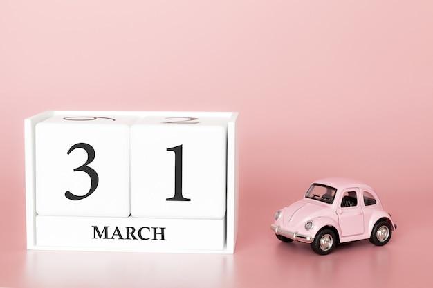 3月31日の木の立方体。 3月の31日目、レトロな車とピンクの背景のカレンダー。
