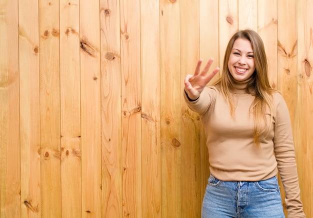 若いブロンドの女性は笑みを浮かべて、友好的な探して、カウントダウンの手で3番目または3番目を示す