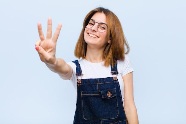 笑顔とフレンドリーな若いきれいな女性、3番目または3番目の手を前方に表示、青い壁に対してカウントダウン