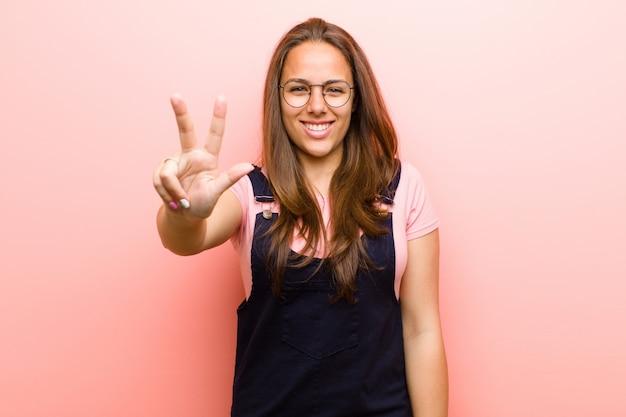 笑顔でフレンドリーな若い女性がピンクの壁にカウントダウン、前方に手で3番目または3番目の数を表示