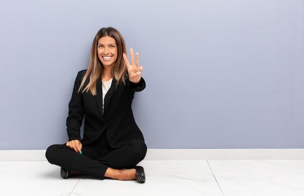 ビジネスコンセプトをカウントダウン、笑顔でフレンドリーな探している若いきれいな女性の手で3番目または3番目の前方を表示