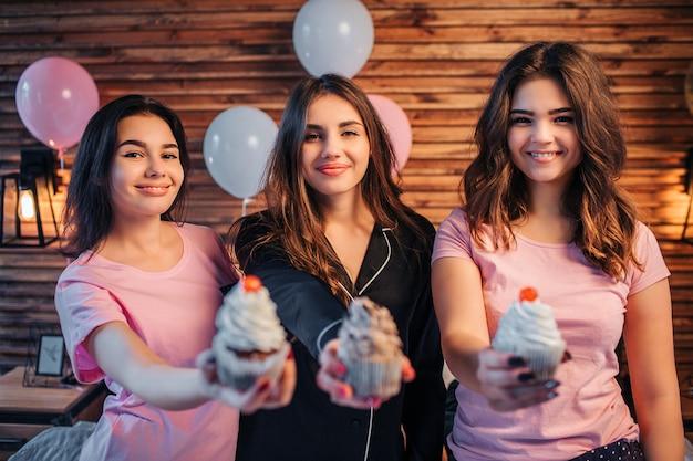 3人の若い女性が立って見ています。彼らは微笑む。人々は3つのケーキを手に持っています。彼らはそれを示しています。美味しそうです。若い女性は部屋でパーティーをしています。