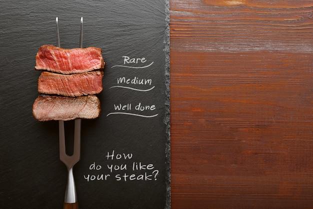 肉用のフォークに3枚の肉。 3種類の肉のロースト、レア、ミディアム、よくできています。