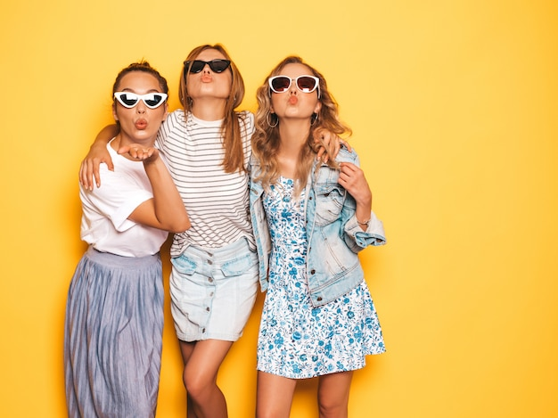 トレンディな夏服で3人の若い美しい笑顔流行に敏感な女の子。黄色の壁に近いポーズセクシーな屈託のない女性。楽しいポジティブモデル。サングラス。3人の若い美人