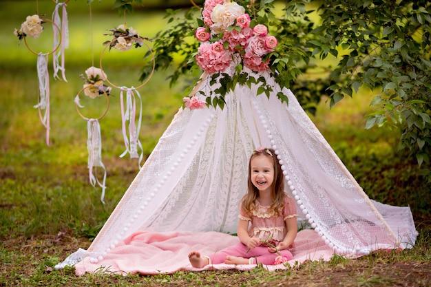 Портрет милой счастливой маленькой девочки 3-4 лет летом в парке в ажурном цветочном вигваме.