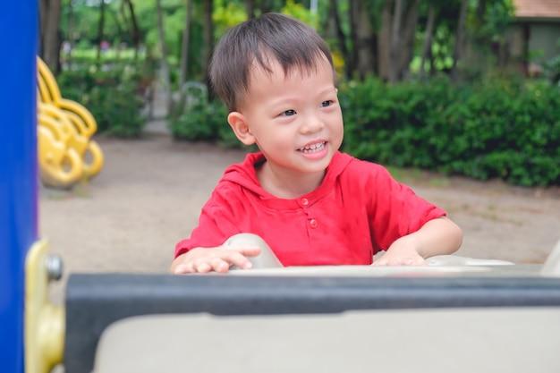 Азиатский малыш от 3 до 4 лет с удовольствием лазает по искусственным валунам на детской площадке в парке
