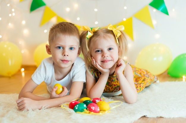 イースターエッグのある明るい服を着た床の上に、3-5歳のかわいい小さな子供たちが胃の上に横たわる
