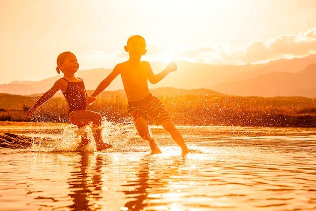 3歳と6歳の2人の子供が海で遊んで、周りに水を噴霧している肖像