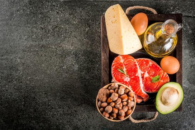 健康的な有機食品。健康的な脂肪を含む製品。オメガ3、オメガ6。成分と製品:マス(サーモン)、オリーブオイル、アボカド、ナッツ、チーズ、卵。暗い石のテーブルの上。 copyspaceトップビュー