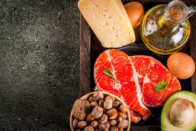 健康的な有機食品。健康的な脂肪を含む製品。オメガ3、オメガ6。成分と製品:マス(サーモン)、オリーブオイル、アボカド、ナッツ、チーズ、卵。暗い石のテーブルの上。コピースペーストップビュー