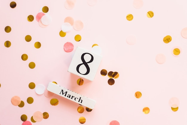 3月8日のシンボル。木製カレンダーと3月のお祝い女性の日のコンセプトは、紙吹雪とピンクの背景の日付8。テキストと広告のための場所