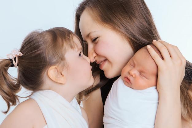 健康的なライフスタイル、子供たちの保護、ショッピング-母親の腕の中で赤ちゃんの概念。子供を抱いた女性。ツリーの女の子。白い背景で隔離されました。コピースペース。 3月8日、母の日