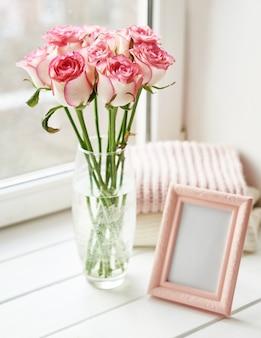 バラの花束とウィンドウ上のフォトフレーム。バレンタインカード。新鮮な花の組成。テキスト用のスペース。母の日と3月8日のカード
