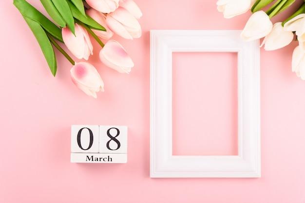 3月8日のカレンダーと上面図チューリップの花とフォトフレーム。幸せな女性の日のコンセプト