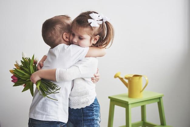 美しい少年と抱擁とチューリップの女の子。母の日、3月8日、誕生日おめでとう