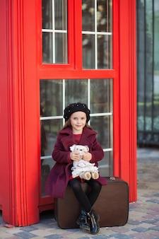 テディベアとスーツケースの上に座っている少女。ロンドンの赤い電話ボックス。春。秋。旅。ロンドン、イギリス。春。国際女性の日とともに。 3月8日から!