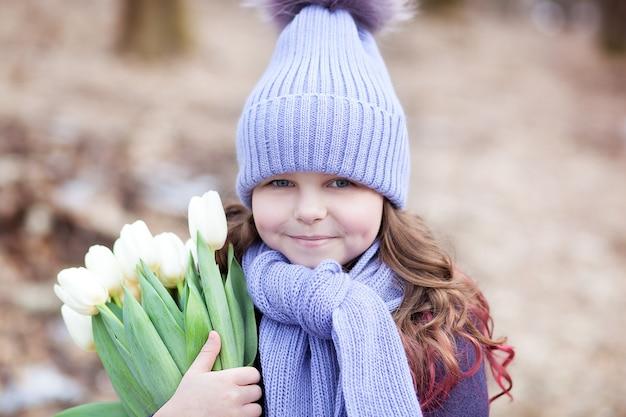 白いチューリップの花束と公園で美しい少女。チューリップの花束。女性の母の日への贈り物としての花。 3月8日。春と女性の日の概念。イースター。クローズアップの肖像画の子