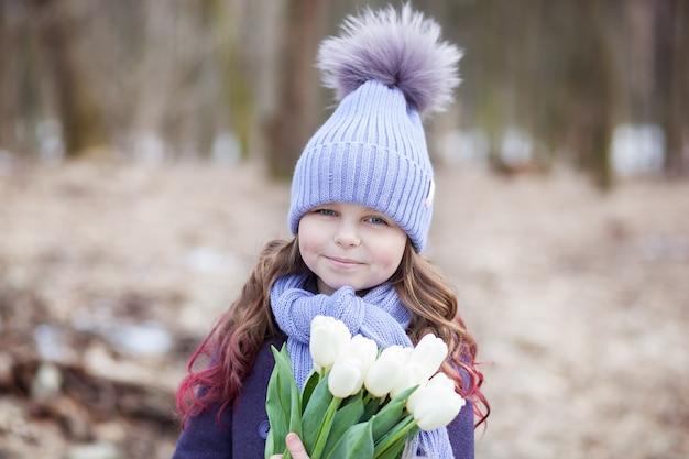 白いチューリップの花束と公園でかわいい女の子。女性の母の日への贈り物としての花。 3月8日。イースター。幸せな母の日の花束を持つ少女。お母さんへの贈り物になります。