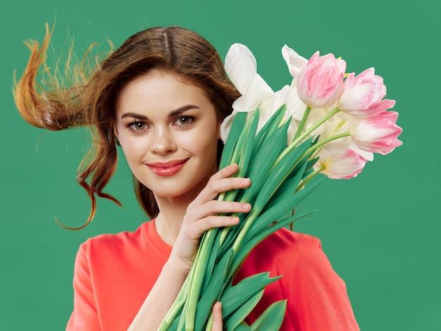 3月8日に花と美しいドレスを着た女性、ギフト花明るい背景バレンタインのスタジオ