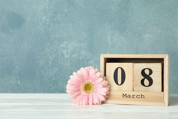 女性の日3月8日、木製ブロックカレンダー。母の日おめでとう。白いテーブルの春の花。テキストのためのスペース