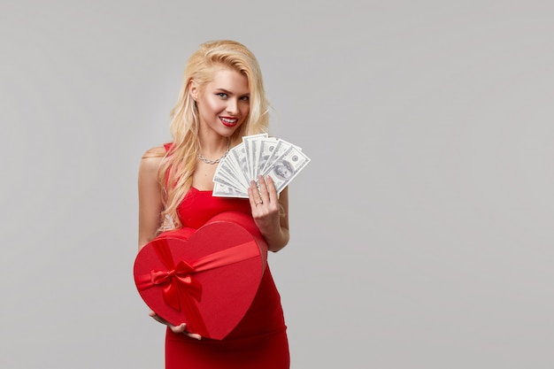 赤いドレスを着た若い女性は、現金紙幣、ドル、ハート型のギフトボックスを手に持っています。バレンタインデーと3月8日