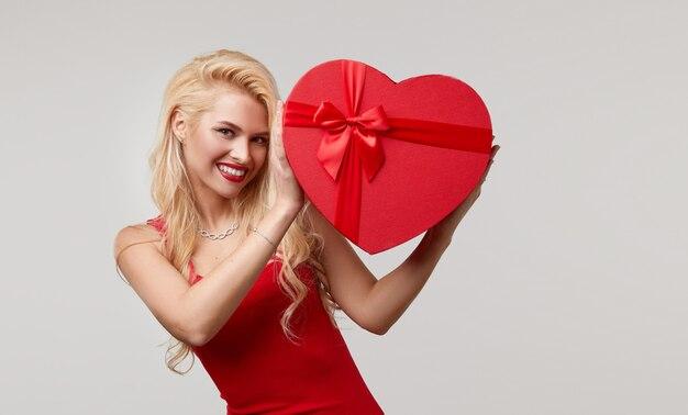 赤いハートのボックスを顔の近くに持っている赤いドレスを着た若い女性。バレンタインデーと3月8日