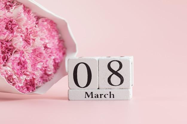 ピンクのカーネーションの花とテキストのコピースペースを持つ3月8日のカレンダー。愛、平等、国際的な女性の日のコンセプト