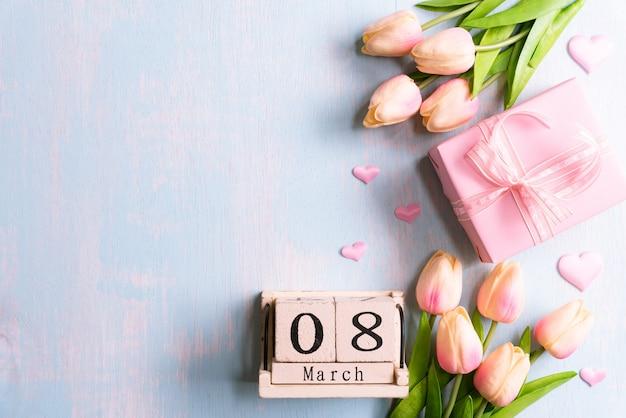 国際女性の日のコンセプトです。ピンクのチューリップと3月8日のテキストと紙の心