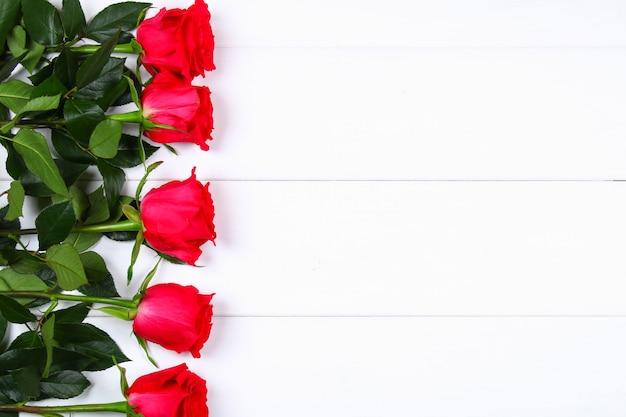 白い木製のテーブルにピンクのバラ。母の日3月8日のコピースペーステンプレート