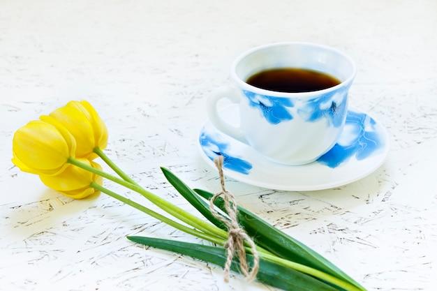 白い背景と花の上のコーヒー。チューリップ。春。朝。 3月8日女性の日