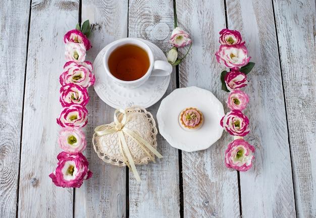 一杯のお茶とレースのハートと美しい花の花束。休日の背景:3月8日、バレンタインデー、母の日、結婚式、婚約