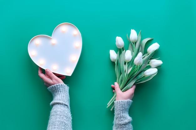 春の幾何学的なフラットは、活気のあるビスケーグリーンミント背景にハート形のライトボードと白いチューリップの花で横たわっていた。母の日、国際女性の日3月8日の装飾。