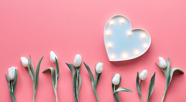 春の幾何学的なフラットは、活気に満ちたピンクのパノラマパノラマ背景にハート形のライトボードと白いチューリップの花で横たわっていた。母の日、国際女性の日3月8日の装飾。