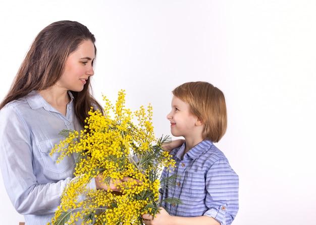 小さな男の子が母親に黄色いミモザの春の花束を贈ります。母の日3月8日、おめでとうございます。