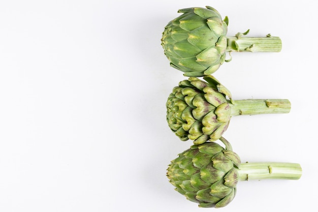 3 artichokes flat lay on a white  free space for your text